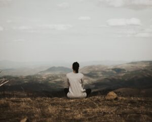 Young woman meditating in the mountains. Reducing teen stress, stressed teen, anxious, nervous, mind management